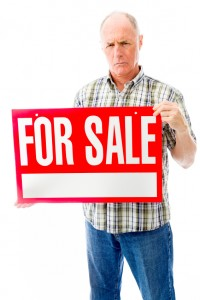 Senior man showing a for sale sign